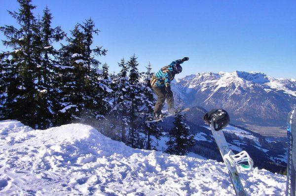 Ein Snowboarder mal eine ordentlichen Sprung, zudem hat man einen schönen Blick ins Tal.