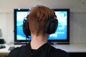 Jugendlicher mit Headset am PC.