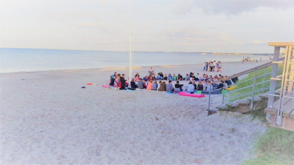 Gruppe im Kreis am Strand