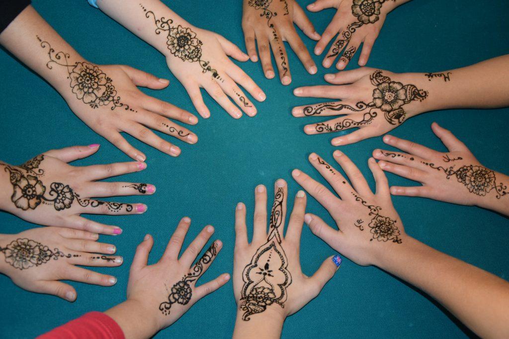 Henna Hände auf einem grünen Tuch.