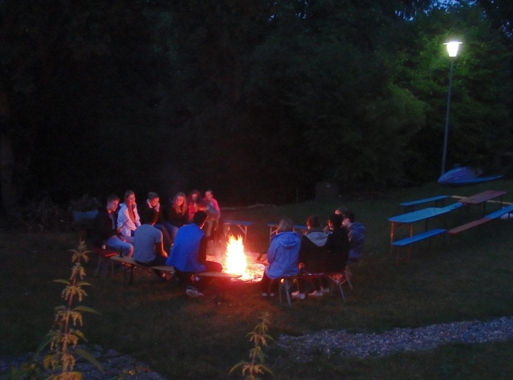 Menschen an einem abendlichen Lagerfeuer.