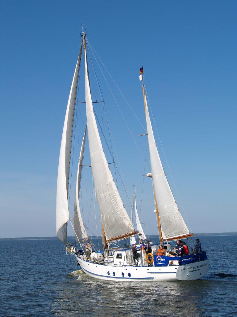Ein Segelboot mit zwei Masten und Besatzung auf See.