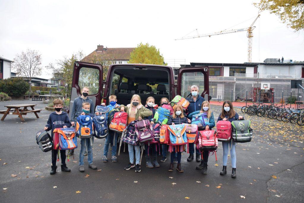 Kinder stehen mit ihrem gebrauchten Schulranzen mit Masken