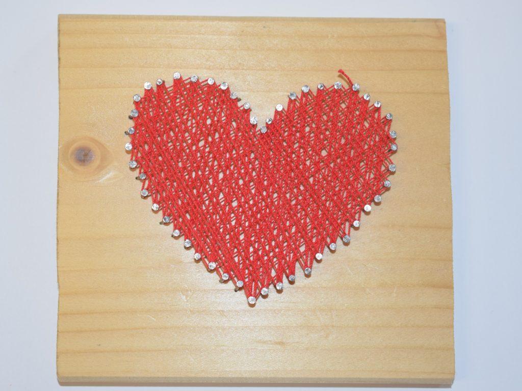 Ein Herz aus Nägeln mit Garn umspannt.