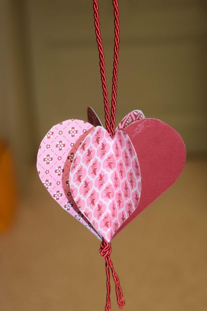 Ein Herzanhänger aus Papier in 3-D-Form.