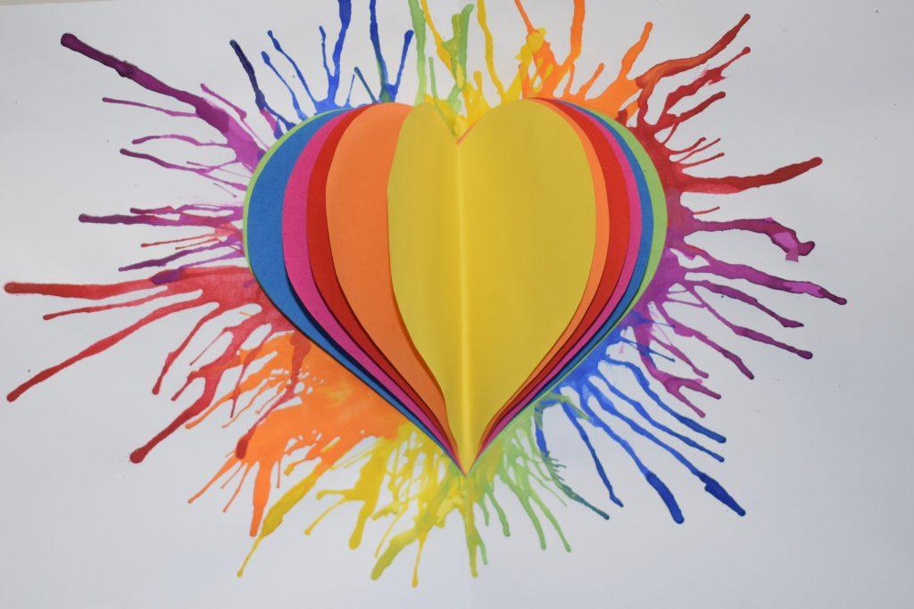 Ein buntes Bild aus Wasserfarben mit Papierherzen in der Mitte