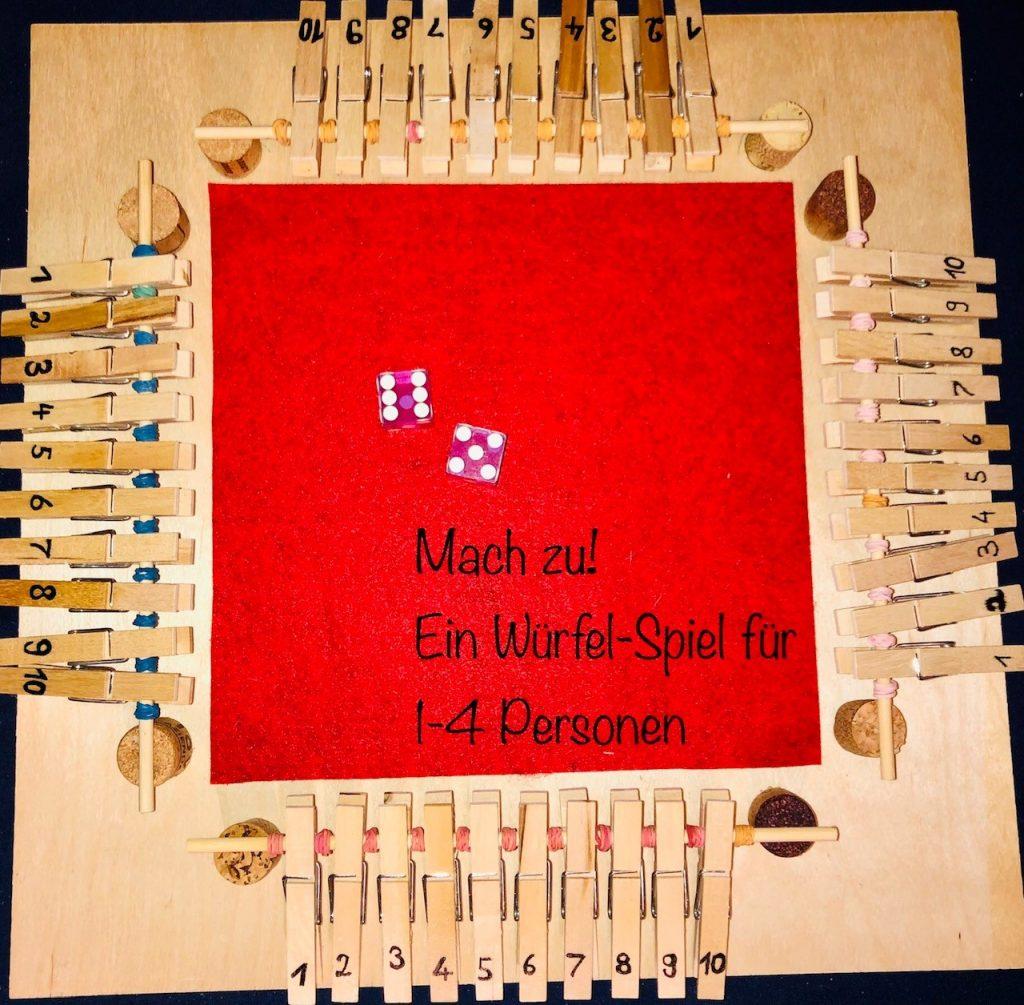 """Spielbrett mit dem Text in der Mitte """"Mach zu! Ein Würfel-Spiel für 1 - 4 Personen""""."""