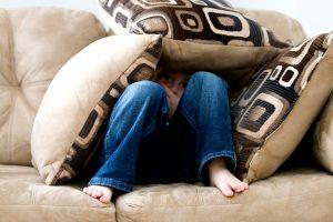 Junge versteckt sich unter Kissen - Bild von ambermb auf Pixabay