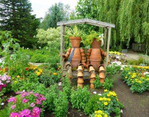 In Blumenbeeten auf einer überdachten Bank sitzen zwei Figuren, die aus zusammengesteckten Blumentöpfen gebildet sind.