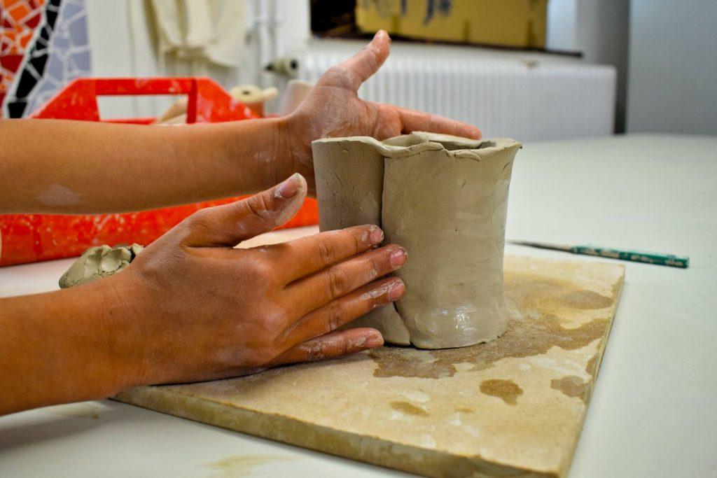 Mit zwei Händen wird ein Gefäß geformt.