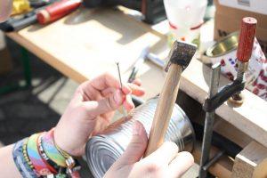 Eine Dose wird mit Hammer und Nagel bearbeitet.