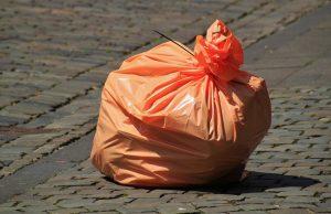 Voller, oranger Müllsack auf Pflastersteinen.