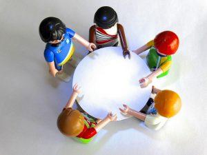 Fünf Playmobilfiguren an einem rundem Tisch
