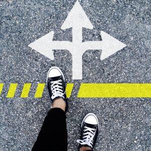 Zwei Turnschuhfüße auf einer gelben Linie vor einem Pfeil, der in drei Richtungen weißt.