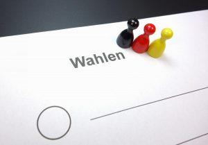 Wahlschein und 3 Spielfiguren, je eine schwarz, rot, gelb
